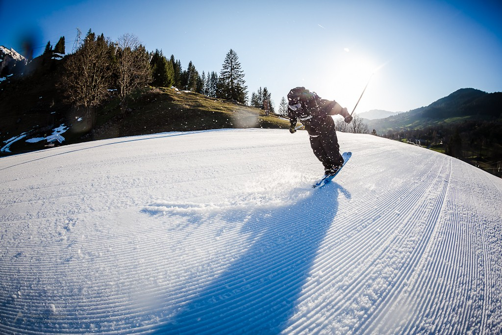 US freeskier Adam Delorme is performing a nose butter 360, on fresh corduroy slope, during 2014 Faction Skis shooting  in La Clusaz Resort, France
